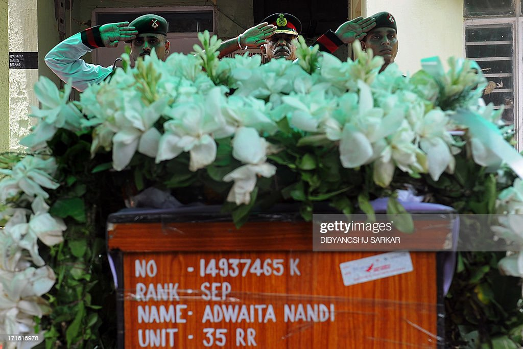 Indian soldiers salute as they pay their respects to fallen comrade Late Sepoy Adwaita Nandi, who was who was killed in Srinagar on June 24 with seven other soldiers, during a ceremony in Kolkata on June 27, 2013. The fallen soldier's widow, 22-year old Piu Nandi, commited suicide following the news of her husband's death. Militants staged an attack June 24 on a troop convoy on the outskirts of Srinagar, killing eight soldiers and wounding 13 others on the eve of a visit by Prime Minister Manmohan Singh. AFP PHOTO/ Dibyangshu SARKAR