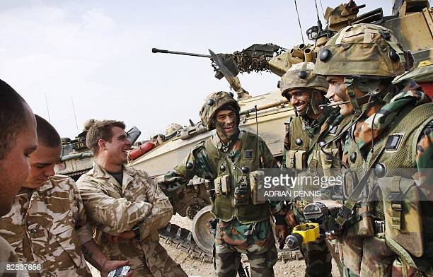 Indian soldiers share a joke with their British counterparts beside armoured fighting vehicles during a joint training exercise with the British Army...