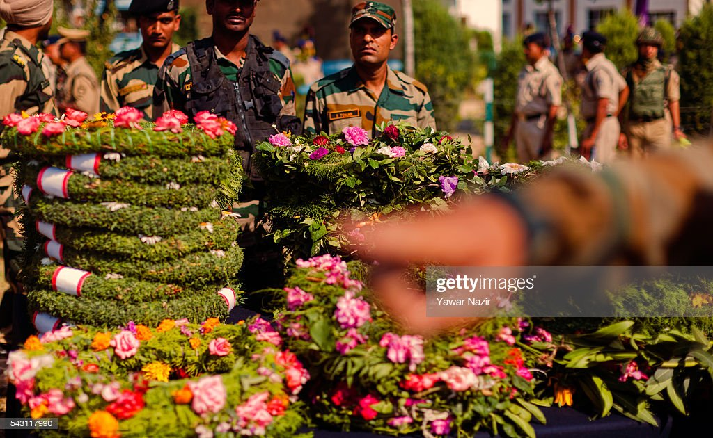 Indian soldiers stand next to the wreaths during the wreath laying of eight Indian Paramilitary soldiers of Central Reserve Police Force (CRPF) killed in an ambush on June 26, 2016 in Srinagar, the summer capital of Indian Administered Kashmir, Indian. Eight Indian Central Reserve Police Force troopers were killed and another twenty critically wounded on Saturday after pro freedom rebels ambushed a paramilitary convoy on the Srinagar-Jammu highway near Pampore in Jammu and Kashmir's Pulwom district, police said. The firing was returned and two rebels were killed in the retaliatory action by the CRPF troopers. A wreath-laying ceremony was held today by the CRPF for their killed comrades.