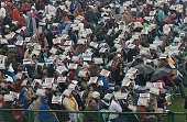 Indian spectators cover themselves with information booklets as it rains during the nation's Republic Day parade on Rajpath in New Delhi on January...