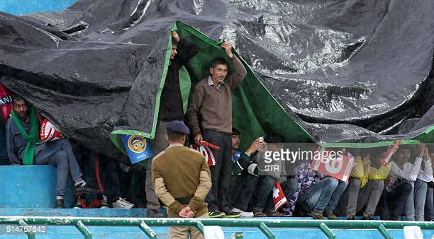 Indian spectators shelter under a tarpaulin as rain falls ahead of the World T20 cricket tournament qualifying match between Oman and The Netherlands...