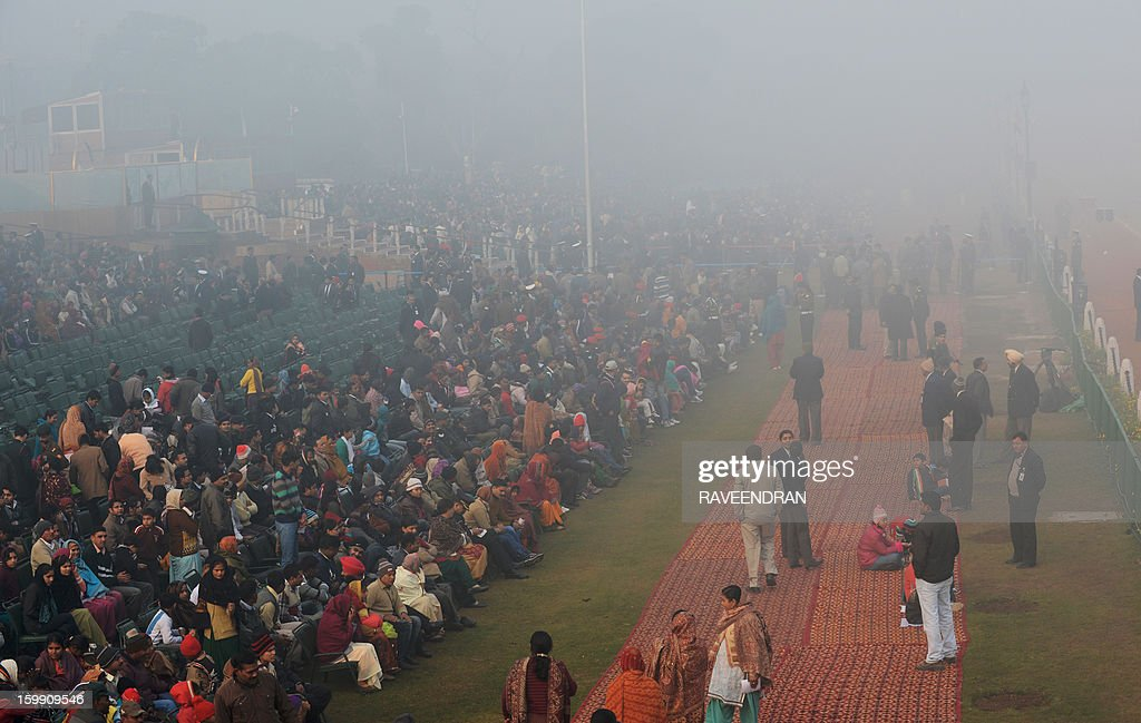 Indian spectators sit in fog before the final full dress rehearsal for the Indian Republic Day parade early in New Delhi on January 23, 2013. India will celebrate the 64th Republic Day on January 26 with a large military parade.