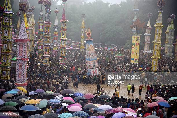 TOPSHOT Indian spectators watch as Pnar or Jaintia tribesmen pull a Rong chariot and dance in muddy waters during the celebration of the Behdienkhlam...