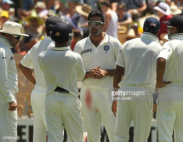 Indian spin bowler Ravi Ashwin speaks with teamates after taking the wicket of Australian opening batsman Ed Cowan on day 1 of the fourth cricket...