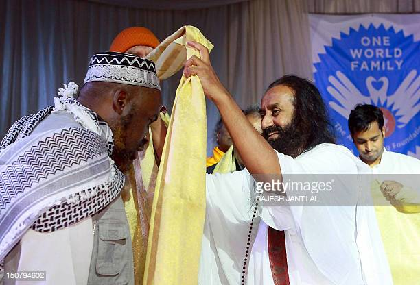 Indian spiritual guru and Art of Living Foundation leader Sri Sri Ravi Shankar places a shall as a mark of respect and blessings on Muslim leader...