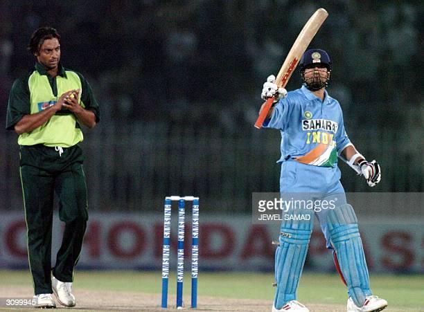 Indian star batsman Sachin Tendulkar rises his bat to acknowledge the crowd as Pakistani speed star Shoaib Akhtar congratulates him for his century...