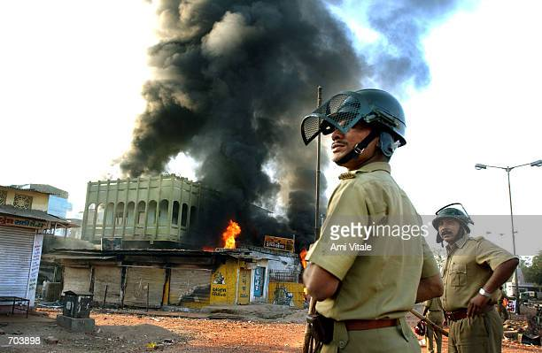 Indian state police watch a Muslim owned shop burn March 1 2002 in Ahmadabad India two days after a Muslim mob attacked a train killing 58 people in...