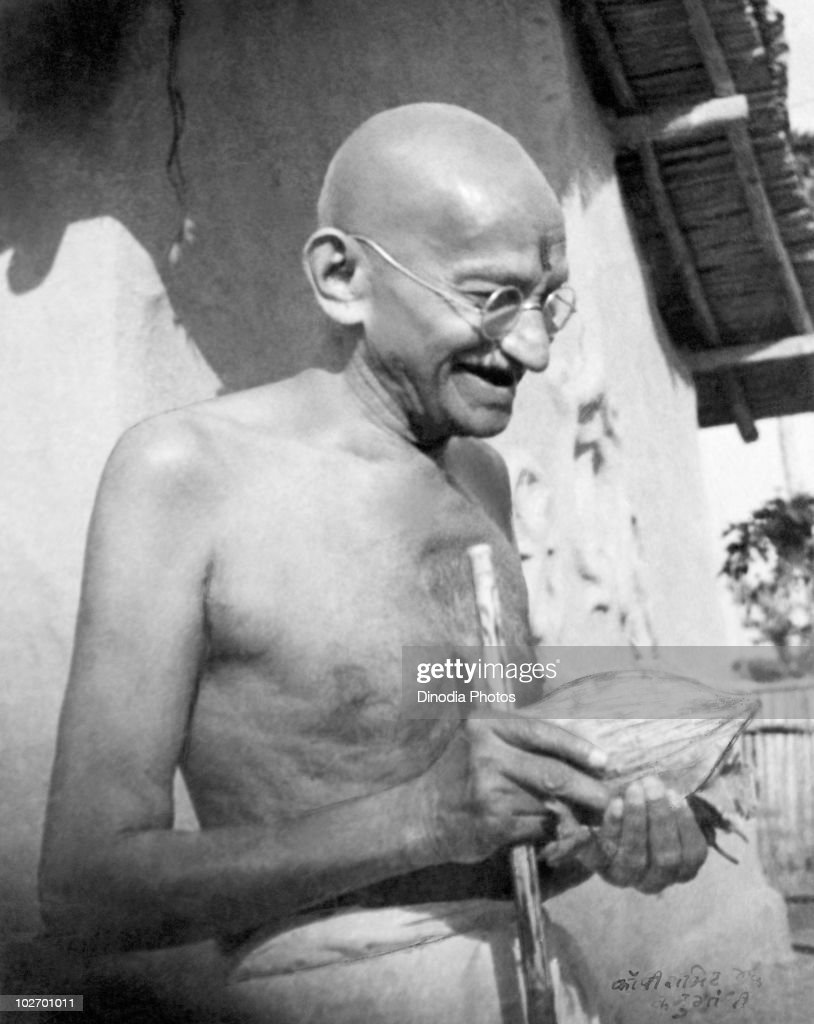 Indian statesman and activist Mohandas Karamchand Gandhi (1869 - 1948) receives a coconut in front of his hut at Sevagram Ashram, January 1942.