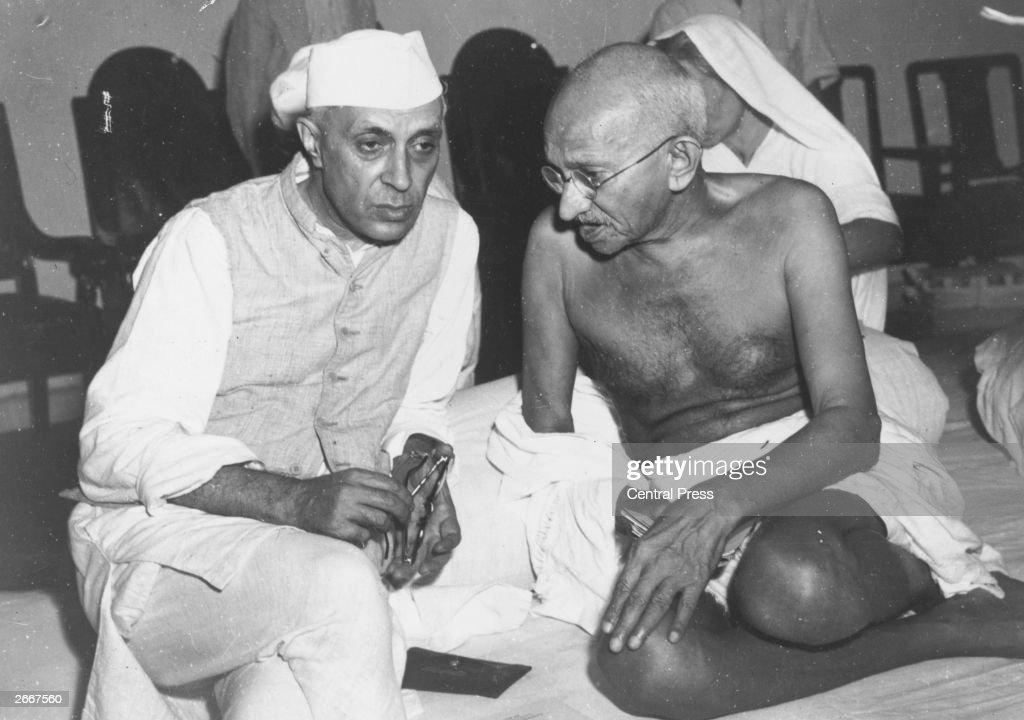 Indian statesmen Mahatma Gandhi (Mohandas Karamchand Gandhi, 1869 - 1948) and Jawaharlal Nehru (1869 - 1964) (left), known as Pandit Nehru, in conversation at the All-India Congress committee meeting at Bombay.