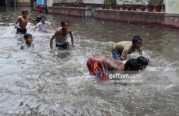 Indian street children swim along a waterlogged street in Kolkata on June 30 2013 Heavy rains in various parts of Kolkata have disrupted normal life...