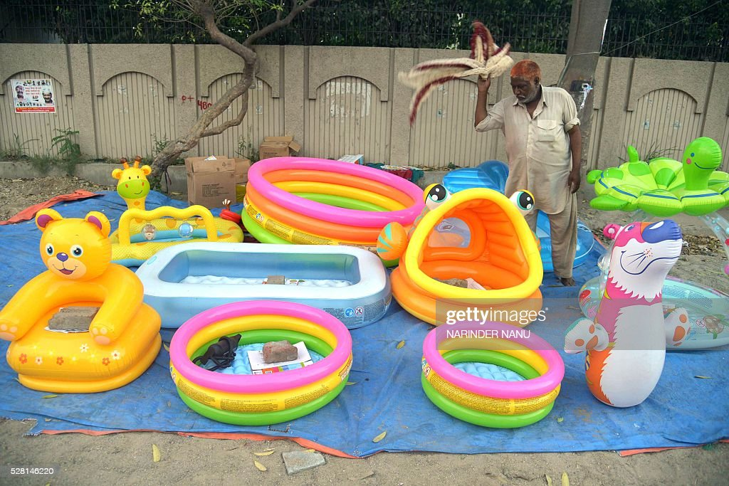 Indian street vendor Hari Singh adjusts his display of paddling pools for sale on a roadside in Amritsar on May 4, 2016. Paddling pools are in heavy demand as residents attempt to beat the heat during the summer season. / AFP / NARINDER