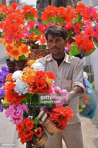 Indian street vendor Mulayam sells artificial flowers from his bicycle in Amritsar on August 23 2014 India's wholesale price inflation hit a...