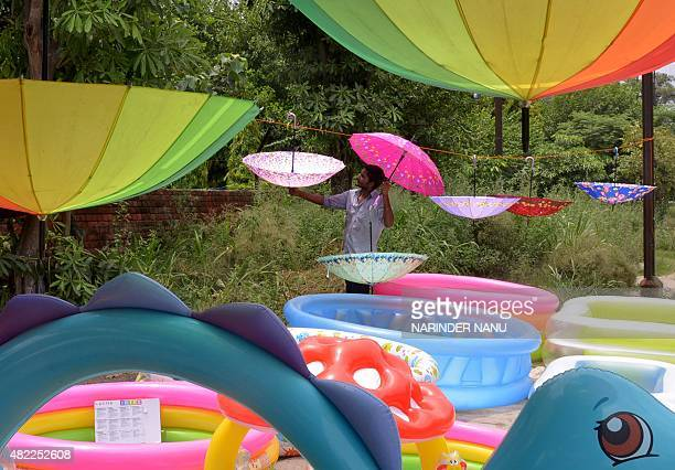 Indian street vendor Vijay adjusts his display of umbrellas and paddling pools for sale on a roadside in Amritsar on July 29 2015 Umbrella are in...