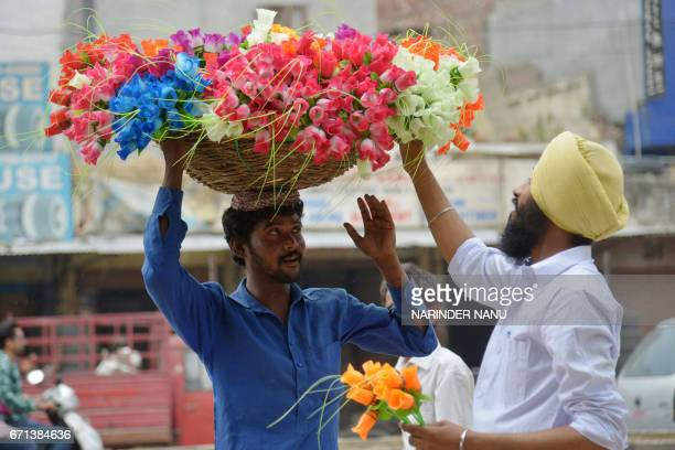Indian street vendor Vijay carries a basket of hand made artificial flowers on his head as he interacts with a customer in Amritsar on April 22 2017...