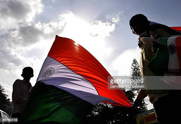 Indian street vendors sell Indian national flags to commuters on the eve of the country's Independence Day in Bangalore on August 14 2009 India will...