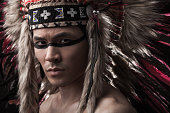 Naked indian strong man with traditional native american make up and headdress looking at the camera. Close up desaturated studio shot
