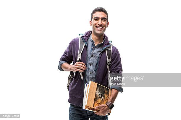 Indian student carrying books and backpack