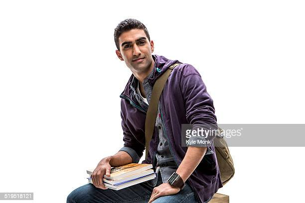 Indian student holding stack of books