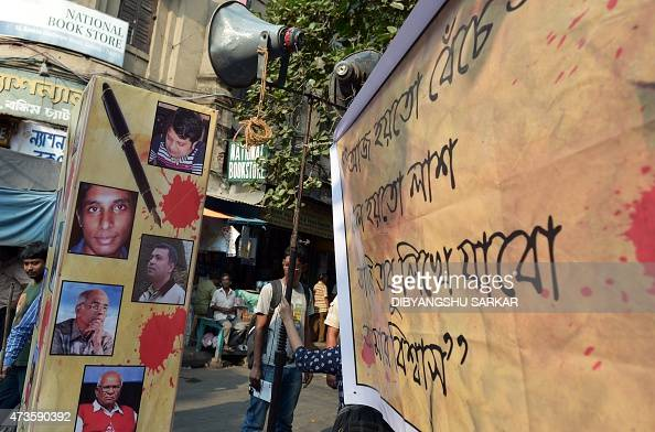 A Indian student looks from behind a poster with pictures of recently killed Bangladeshi bloggers during a protest meeting organised to pay homage in...