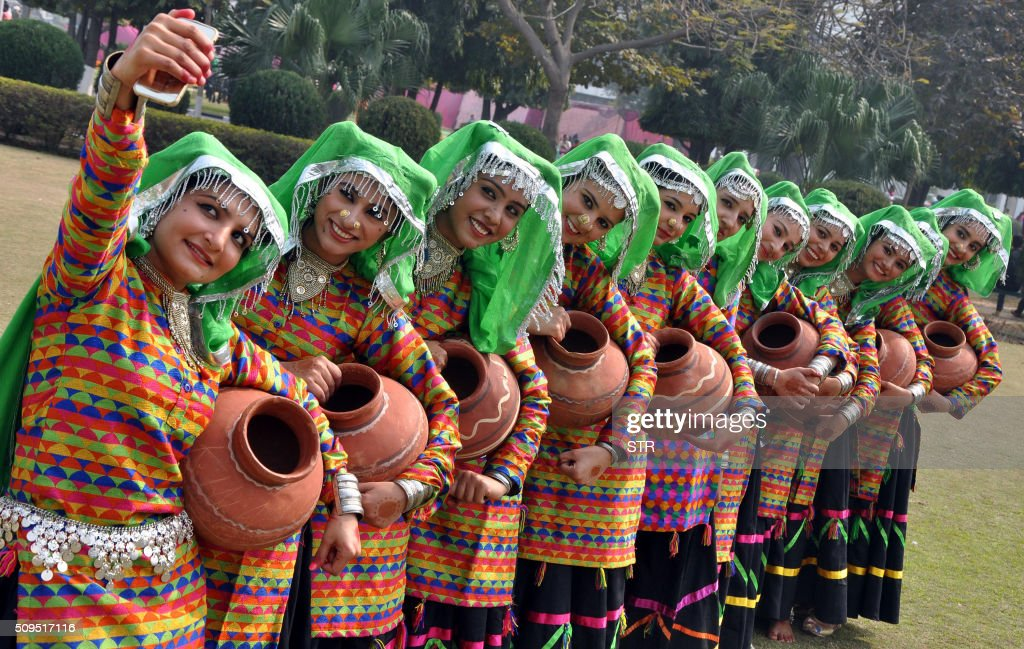 Indian student members of a folk dance group take a selfie photograph with a mobile phone at Punjabi University in Patiala on February 11, 2016. India notched up its billionth mobile phone subscriber in October, the country's telecoms regulator said in late 2015, underscoring the importance of its fast-growing mobile market, the world's second largest after China. AFP PHOTO / AFP / STR