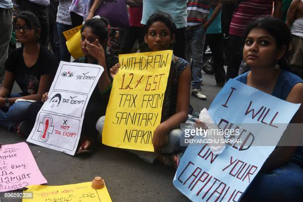 Indian students hold posters and sanitary napkins during a protest over a 12 percent tax on sanitary pads as part of the Goods and Services Tax in...