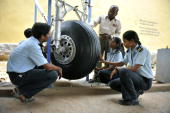 Indian students of Aircraft Maintenance Engineering listen to their instructor during a practical training session with the nose wheel of an aircraft...