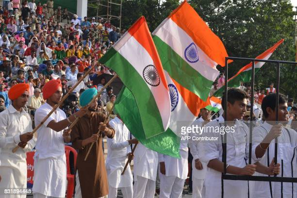 Indian students perform during a ceremony to mark India's 70th Independence Day celebrations at the IndiaPakistan Wagah border post on August 15 2017...