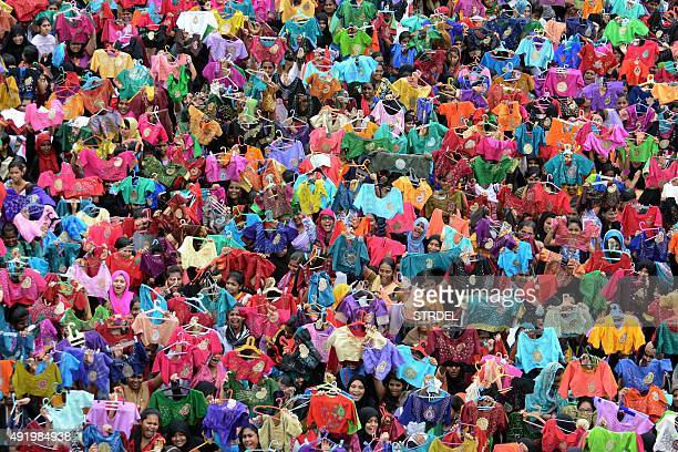 Indian students pose for photographers as they hold up painted and decorated blouses at a college in Chennai on October 9 2015 Some 3500 students...