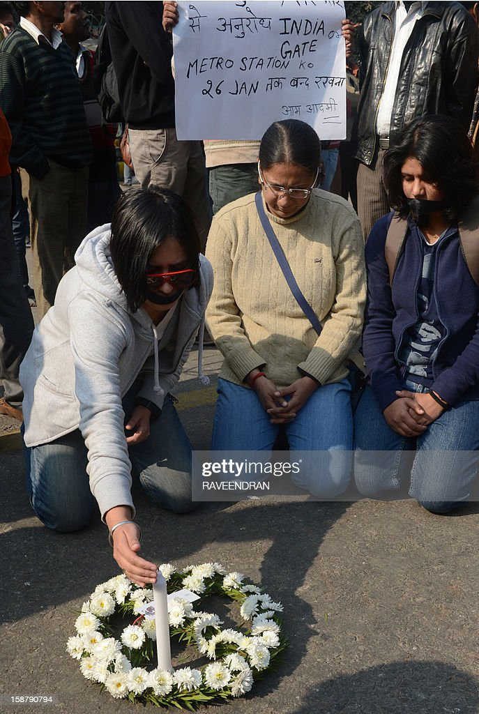Indian students protestors light a candle as they pray for a rape victim during a protest demanding better security for women in New Delhi on December 29, 2012, as Indian leaders appealled for calm fearing fresh outbursts of protests after the death of a gang-rape student victim. New Delhi's top police officer and chief minister have urged people to mourn the death of a gang-rape victim in a peaceful manner as large parts of the city-centre were sealed off. The calls for calm came after an Indian woman who was gang-raped on a New Delhi bus died in a Singapore hospital after suffering severe organ failure.