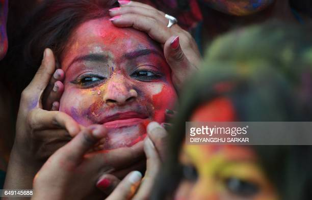 TOPSHOT Indian students smear coloured powder at an event to celebrate the Hindu festival of Holi in Kolkata on March 7 2017 Holi the popular Hindu...