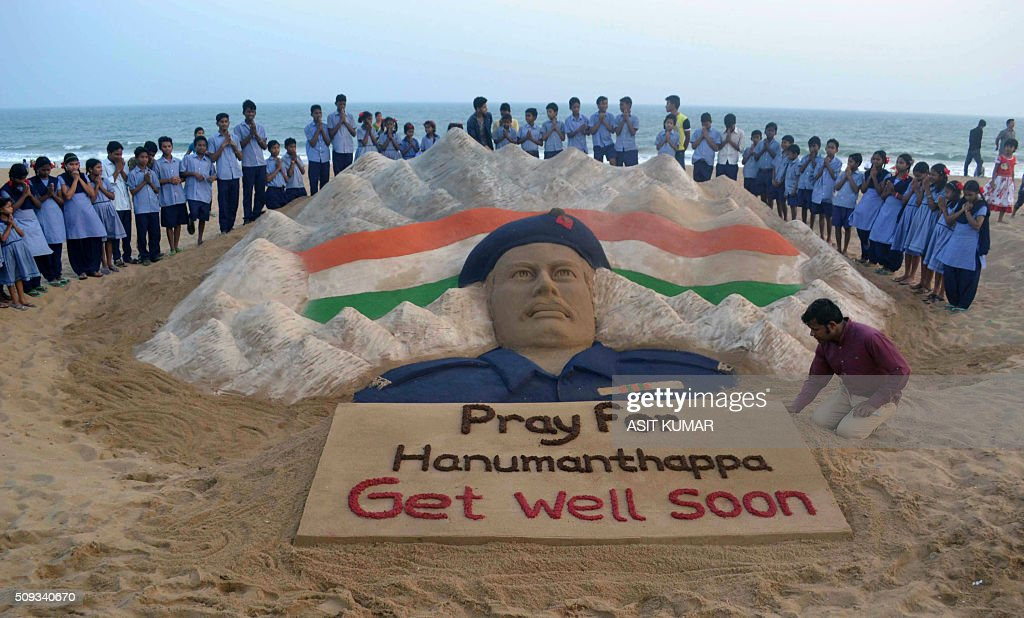 Indian students stand and pray near a sand sculpture created by Sudarsan Pattnaik of Hanumanthappa Koppad, rescued alive five days after being buried in an avalanche in the Himalayas, at Puri beach, some 65 km from Bhubaneswar, on February 10, 2016. An Indian soldier's condition deteriorated February 10, two days after his dramatic rescue from under mounds of snow nearly a week after being buried alive in an avalanche, the army said. AFP PHOTO/ASIT KUMAR / AFP / ASIT KUMAR