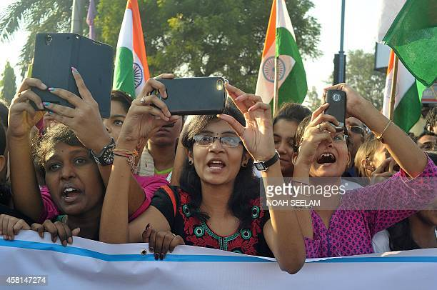 Indian students use cellphones to photograph unseen Central Home Minister of India Rajnath Singh during a Run for Unity event to mark the anniversary...