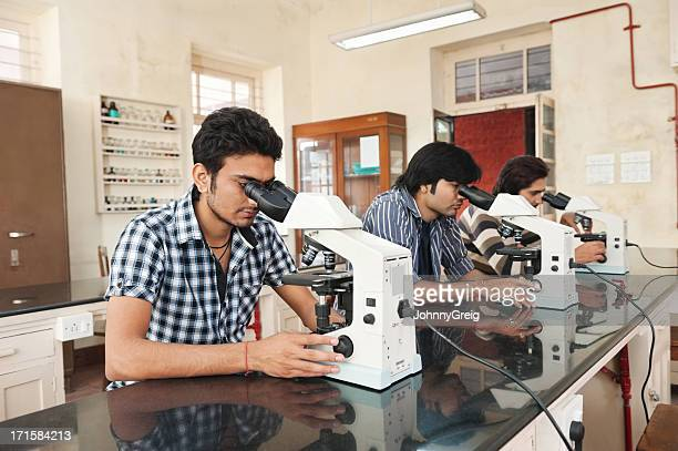Indian Students Using Microscope In Science Laboratory.