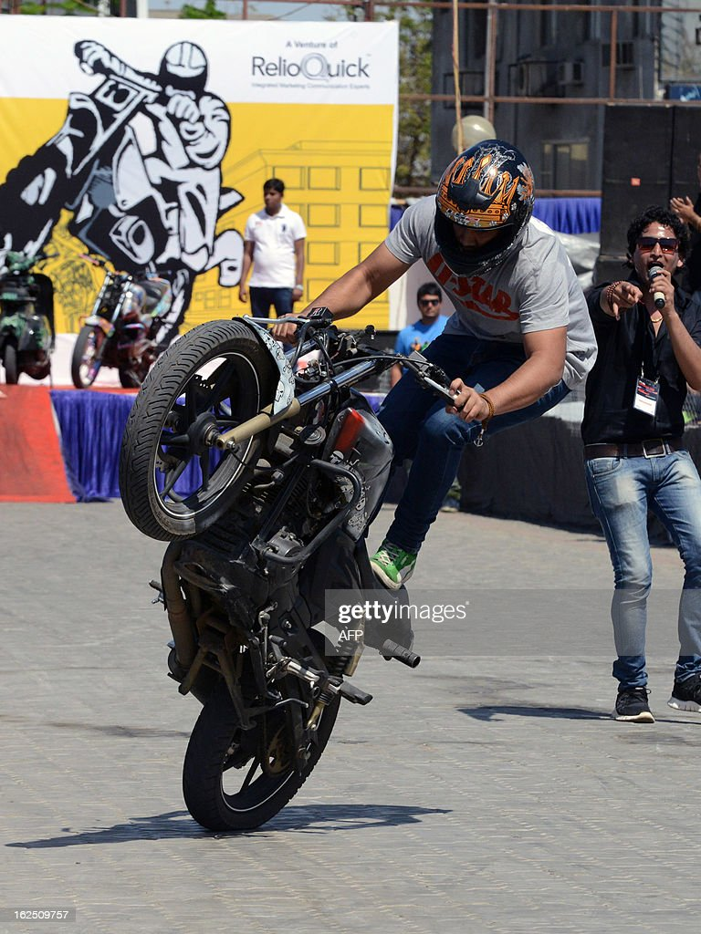 Indian stunt biker Babar Khan performs during a style biking event at the ReliQuick Auto Mall in Ahmedabad on February 24, 2013. Auto exhibition displayed a variety of cars, two wheelers and off-road vehicles. AFP PHOTO / Sam PANTHAKY