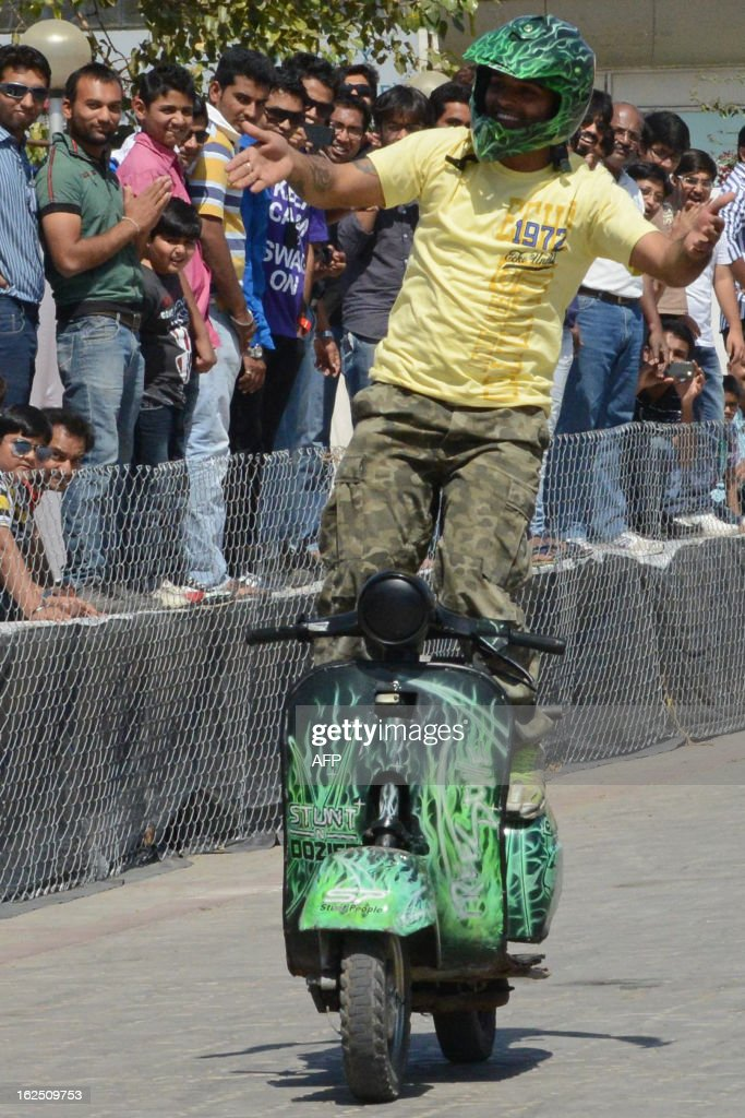 Indian stunt biker Dinesh Verma from Bhopal performs on his scooter during a style biking event at the ReliQuick Auto Mall in Ahmedabad on February 24, 2013. Auto exhibition displayed a variety of cars, two wheelers and off-road vehicles. AFP PHOTO / Sam PANTHAKY