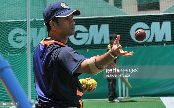 Indian superstar cricketer Sachin Tendulkar practices with his son Arjun at Newlands Stadium in Cape Town on Janurary 1 2011 on the eve of the third...