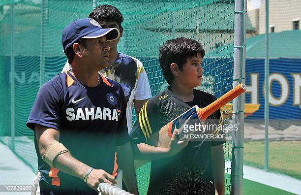 Indian superstar cricketer Sachin Tendulkar talks with his son Arjun during a training at Newlands Stadium in Cape Town on Janurary 1 2011 on the eve...