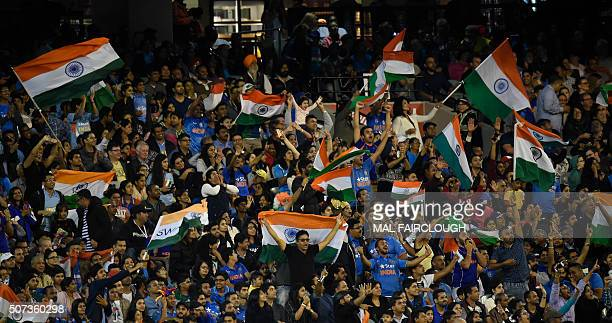 Indian supporters cheer and wave flags during the second Twenty20 international cricket match between Australia and India at the MCG in Melbourne on...