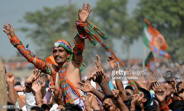 Indian supporters cheer as Prime Minister Narendra Modi delivers a speech during an election rally in Aurangabad in Bihar on October 9 2015 Voting...