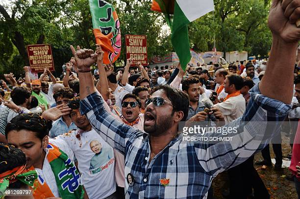 Indian supporters of Bharatiya Janata Party leader and prime ministerial candidate Narendra Modi celebrate at the party headquarters in New Delhi on...