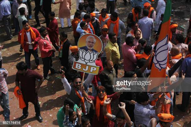 Indian supporters of Bhartiya Janta Party celebrate after election results outside the party state head quarter in Lucknow capital and largest city...