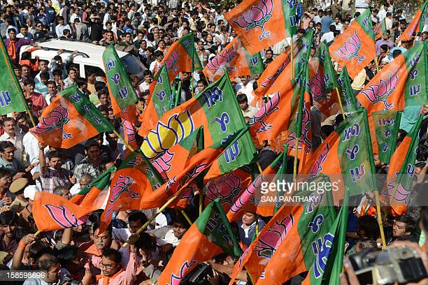 Indian supporters of Bhartiya Janta Party holding BJP flags celebrating the Gujarat Assembly election results being declared in Ahmedabad on December...