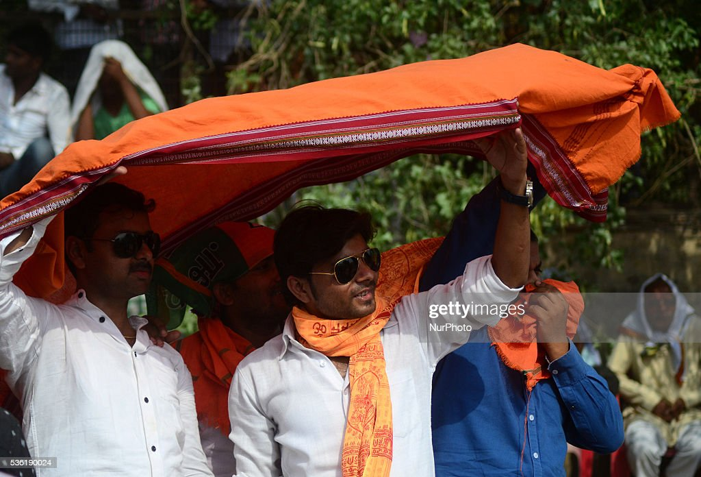 Indian supporters of Bhartiya janta party (BJP) listen to national president of BJP Amit Shah's speech during scorching hot day in Sardar Patel Kisan rally, in Allahabad on May 31,2016.