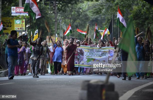 Indian supporters of Gorkhaland movement chant slogans as they hold broomsticks at Sukna village in Darjeeling district on the outskirts of Siliguri...