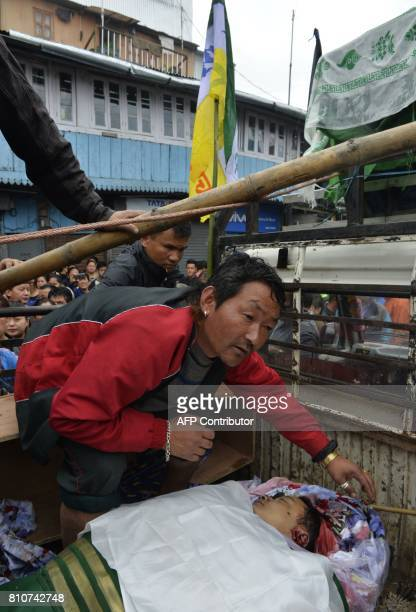 Indian supporters of Gorkhaland transport atop a vehicle the dead body of Tashi Bhutia who is claimed to be killed by police firing during clashes...