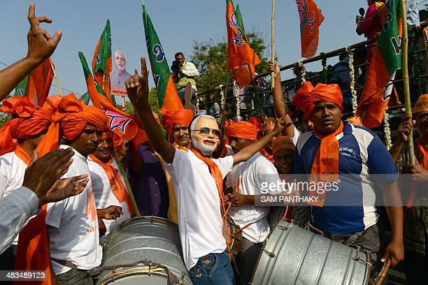 Indian supporters of Gujarat state Chief Minister and Bhartiya Janta Party 's prime ministerial candidate Narendra Modi wear a Modi mask as they...