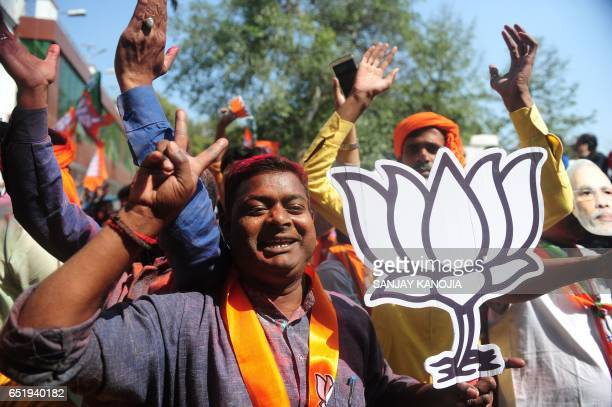 Indian supporters of the Bharatiya Janata Party celebrate outside the party office as state assembly votes are counted in Lucknow on March 11 2017...