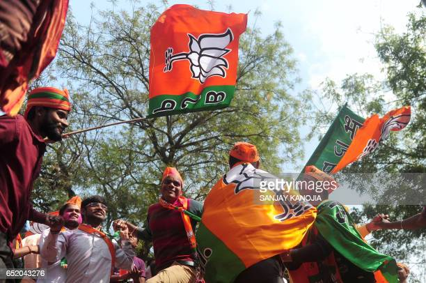 Indian supporters of the Bharatiya Janata Party celebrate outside the party office as state assembly votes are counted in Lucknow on March 11 2017 /...