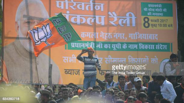 Indian supporters of the Bharatiya Janata Party listen as Prime Minister Narendra Modi speaks during a election rally in Ghaziabad