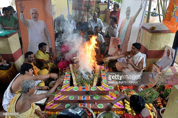 Indian supporters of the Bharatiya Janatha Party perform 'yagya' the sacred Hindu fire ritual for the BJP prime ministerial candidate Narendra Modi...